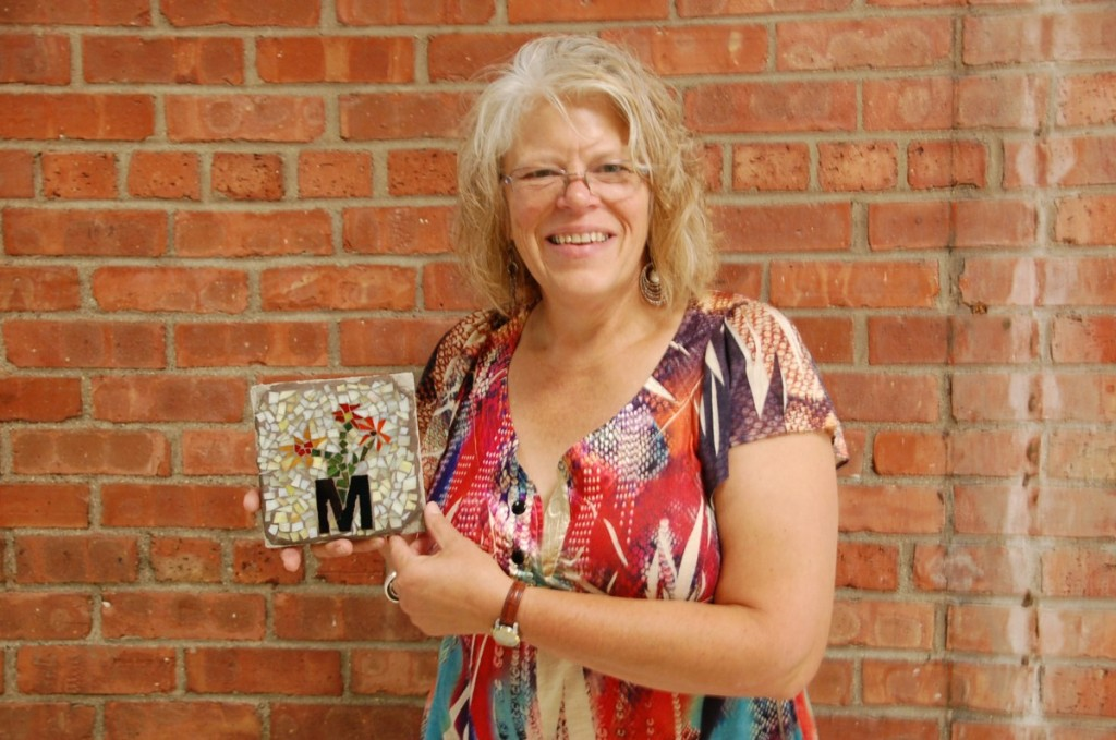 Spearheading the Badger Heritage Wall project, Sherri Kruger holds up one of the family tiles, decorated with the family initial and in a design reflecting the specific family. A mosaic artist for the past 20 years, Kruger wanted to do something larger, like public art, and decided to do so by starting this project, a task allowing her to give back to a community that has given her a job and a home and a community to create a place to share its story to anyone passing by it along Highway 11. (photos by Ryan Bergeron)