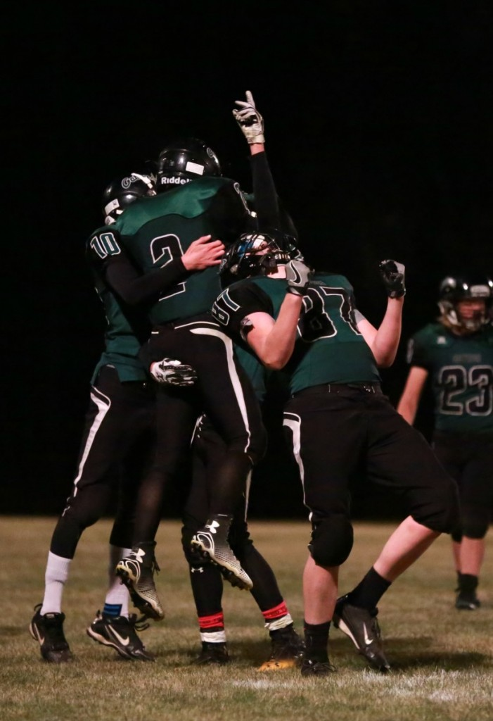 Gator players Michael Olson (#10), Logan Anderson (#2), Tanner Foss (behind Anderson), and Shaun Waage (#87) celebrate after the comeback win over Blackduck on October 19 in Middle River. (photo by Val Truscinski)