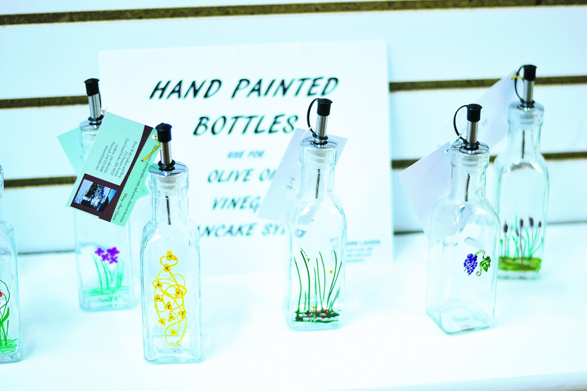 Hand painted bottles by Mary AnnLaxen. All proceeds from sales are sent to Haiti. (photo by Serianna Henkel)
