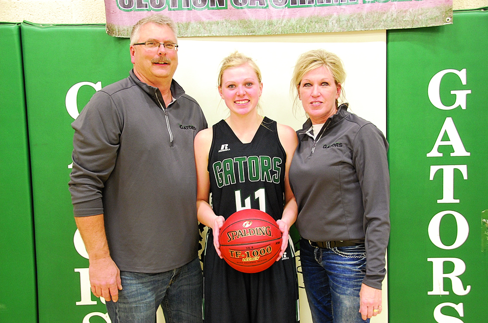 photo by Ryan Bergeron Gator junior Carly Mekash poses for a photo with her parents Dale and Shellie Mekash after the home game versus KCC on December 5, a game where she hit her 1,000 point. Needing six points to reach the milestone, Mekash finished with a team-high 13 points in the Gator girls 61-51 defeat.