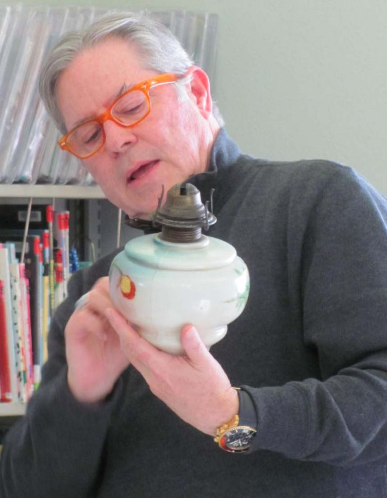 "Antique appraiser Mark Moran, who has appeared on the ""Antiques Road Show"" PBS series, studies the type of art work on a kerosene lamp."