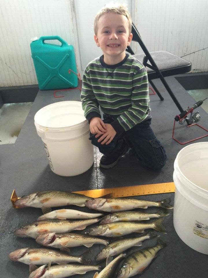 young boy enjoying a pile of fish with dad