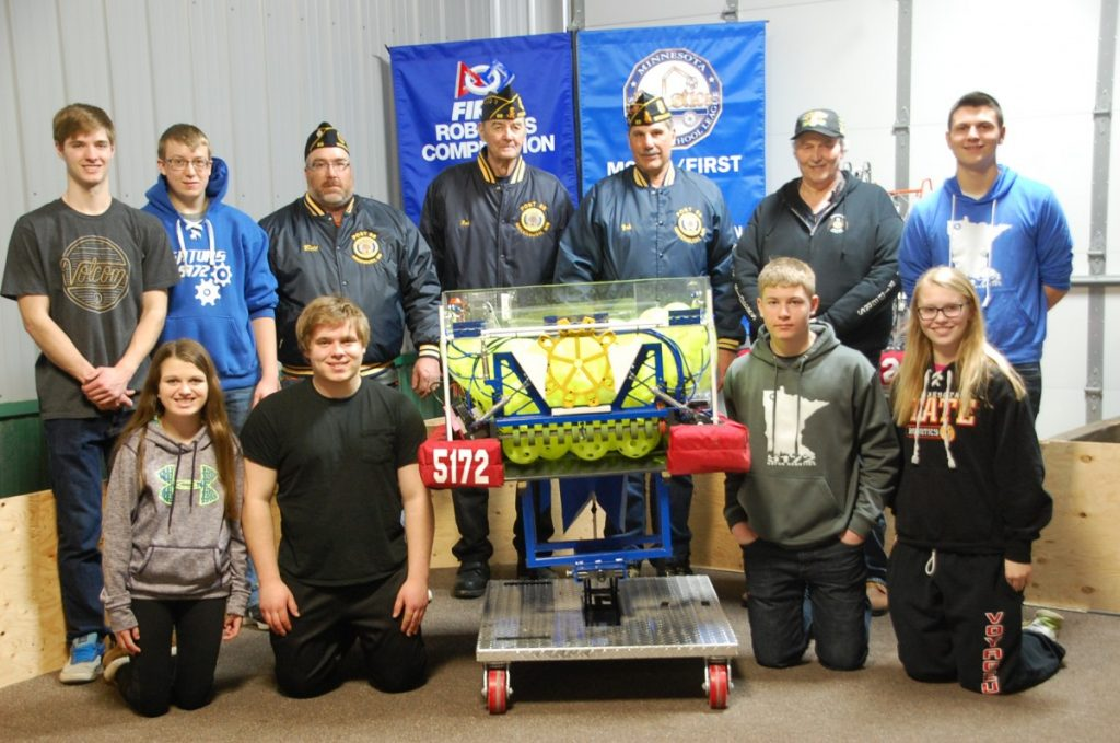 Some members of the Gator Robotics team pose for a photo with Greenbush Legion members in-between the practice session with the Badger Robotics team on February 19  in honor of the legions's sponsorship to the team. Front: Emily McLean, Robert Hlucny, Kyle Stauffenecker, Hannah Anderson. Back: John Langaas, Kyle Stenberg, Bill Timm, Rodney Langaas, Robert Novacek, Stanley Melby, and Blake Dallager. (photo by Ryan Bergeron)
