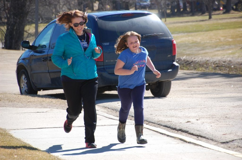GMR teacher Ashley Duray and second-grade GMR student Tarson Erickson finish out the last lap during a Mighty Milers run on a sunny 50-plus-degree day after school in Middle River on April 6. Erickson achieved the highest award milestone in Mighty Milers so far this year at GMR, having earned the first marathon medal for completing 26.2 miles, the length of a marathon.