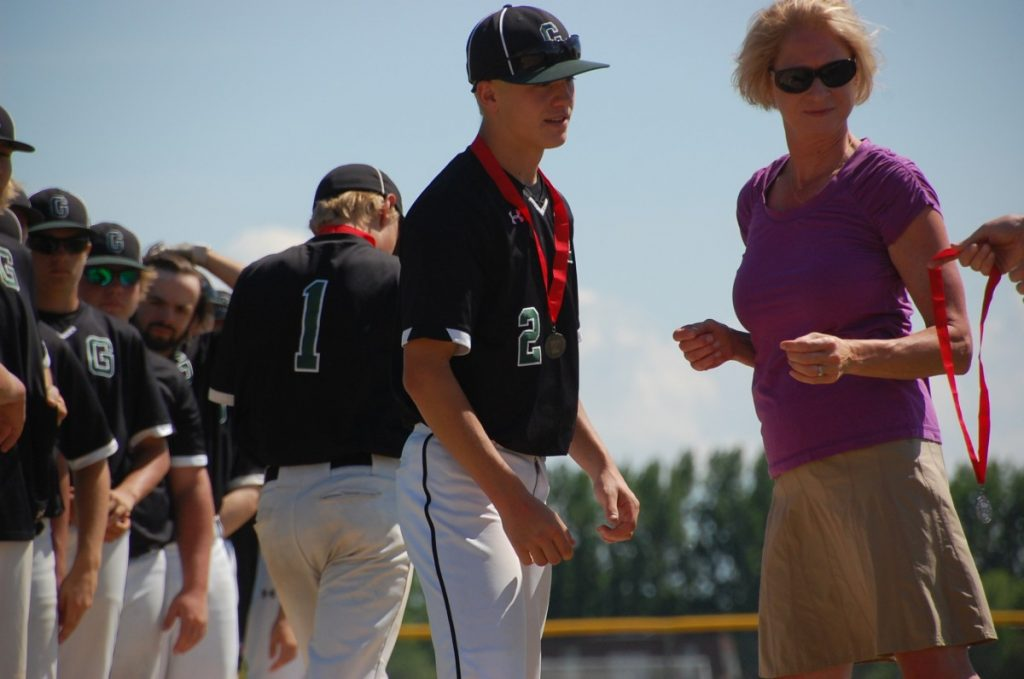 Sharon Schultz (right) hands out runner-up medals following the Gator baseball team's Section 8A championship loss. As the GMR District's new activities director, she looks forward to being even more a part of the Gator atmosphere.