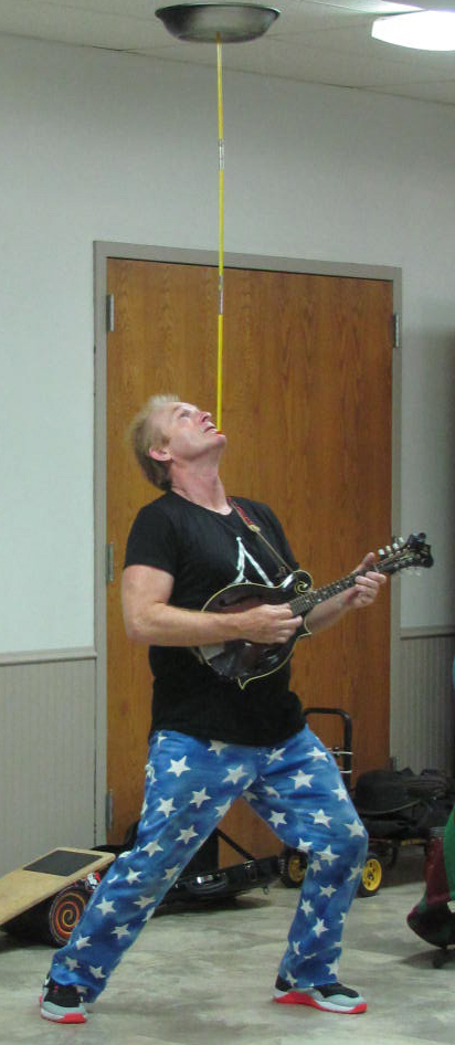 Sean Emery wowed his audience by balancing a dish on a pole that was positioned on his chin while, at the same time, playing a mandolin. (photo by Mavis Gonshorowski)