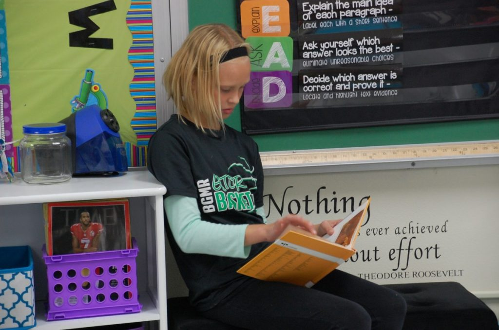 """Brooklyn Wahl reads on a bench in Mrs. Waage's fifth grade """"flexible learning"""" classroom environment last fall. GMR students from third grade to twelfth grade opened up about their school, from their favorite subjects and reasons they enjoy going to school at GMR most to some improvements they'd like to see at their school and some of the issues brought up within the district in recent years."""