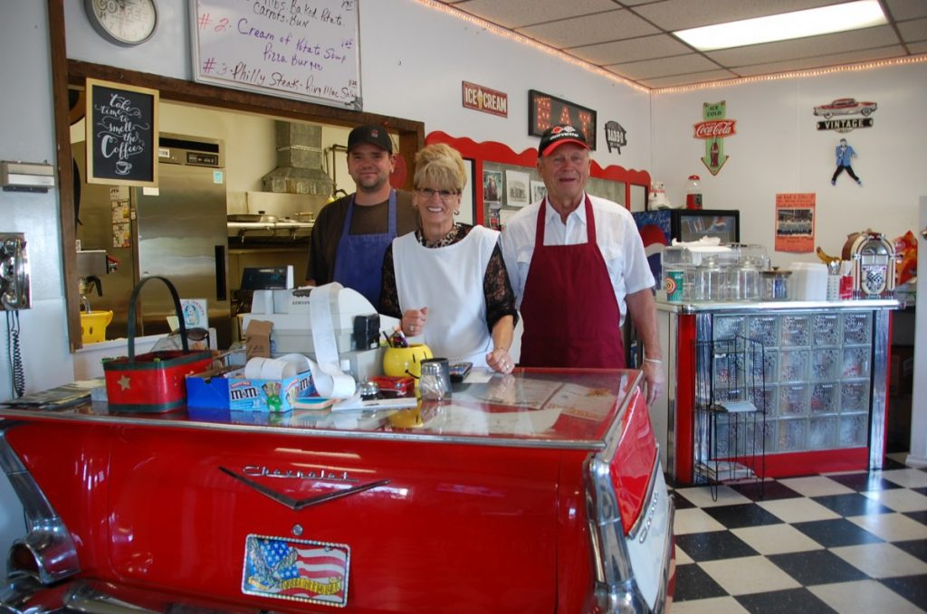 John Wirta, Barb Burkel, and Twins Corner Café owner Ronnie Howell pose for a photo at the counter of the local café located on the corner of Main Street and University Avenue in Badger. A retired farmer, Howell bought the Twins Corner Café in October 2013, at 72 years of age. (photos by Ryan Bergeron)