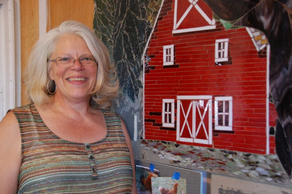 Sherri Kruger stands next to a red barn, one of her favorite parts of the Badger Heritage Wall, a project she started and is currently, with the help of others, putting together. A groundbreaking ceremony for this wall will take place at its new location right behind Border State Bank in Badger at 4-5 pm during the city's annual Fall Fest celebration on September 16. (photos by Ryan Bergeron)