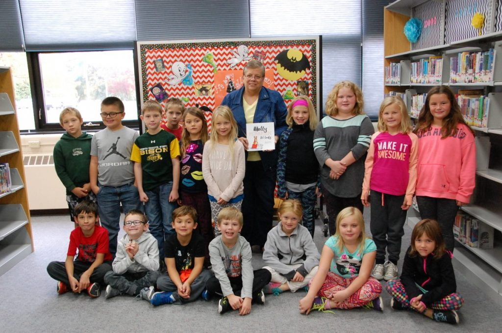 "Deb Koebernick's second grade Greenbush/Middle River class poses for a photo with area author Janice McAlpine (holding the book) after she read them her first published book, ""Molly McPherson 1st Lady"", and answered some of their questions. McAlpine visited and read her book to GMR students in kindergarten to sixth grade and also encouraged writing skills on Wednesday, October 4 in the Greenbush school site library."