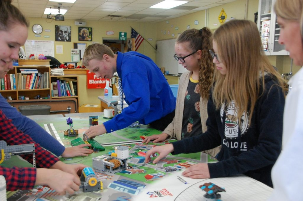 Some members of the Greenbush-Middle River Hatchlings LEGO robotics team set up some of the LEGO pieces atop their practice competition mat. This team includes not only a build team, but also a core values team and a research team, providing team members with different opportunities.