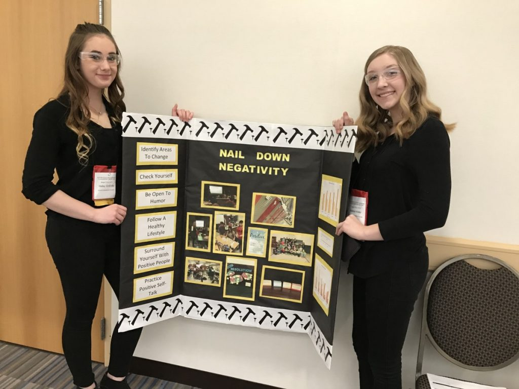 "Badger eighth-grade FCCLA students Hailey VonEnde and Kadeyn Keller show the board depicting their ""Interpersonal Communication"" project titled ""Nail Down Negativity"", an effort focused on promoting more positivity in their school. They advanced to the National Conference in Atlanta with this project. (photo submitted by Gretchen Lee)"