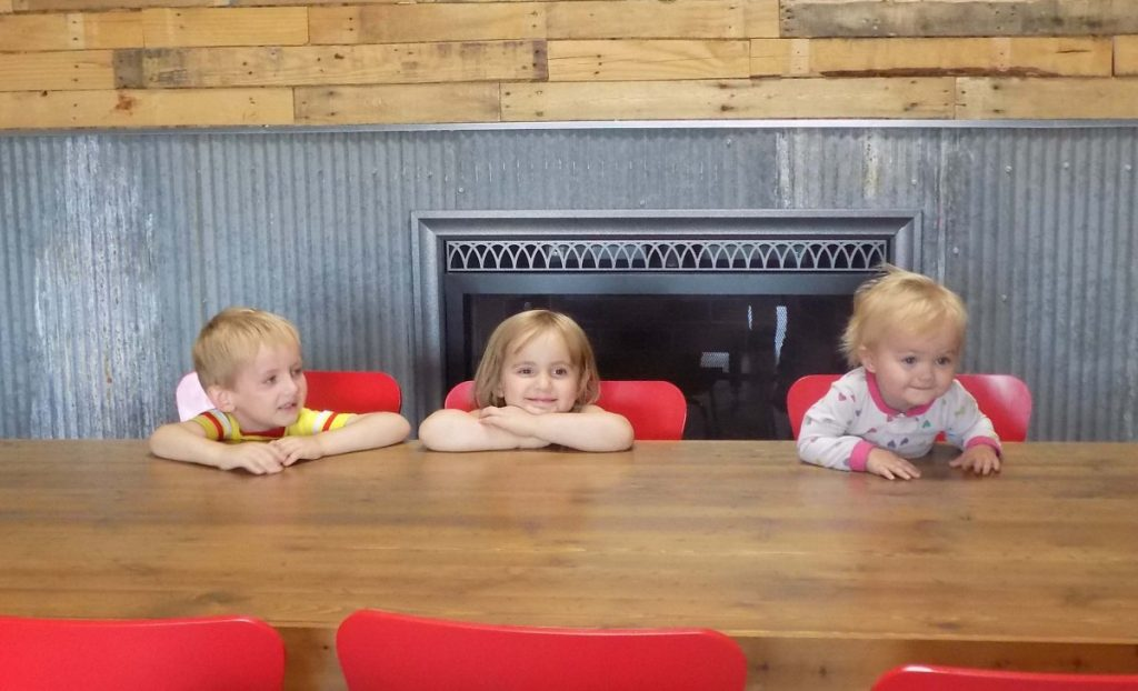Heidi Sather's grandchildren are shown at the farmhouse style table their grandma made. Left to right are Ezekiel, Kilah, and Aineleigh Sather. (photo by Mavis Gonshorowski)