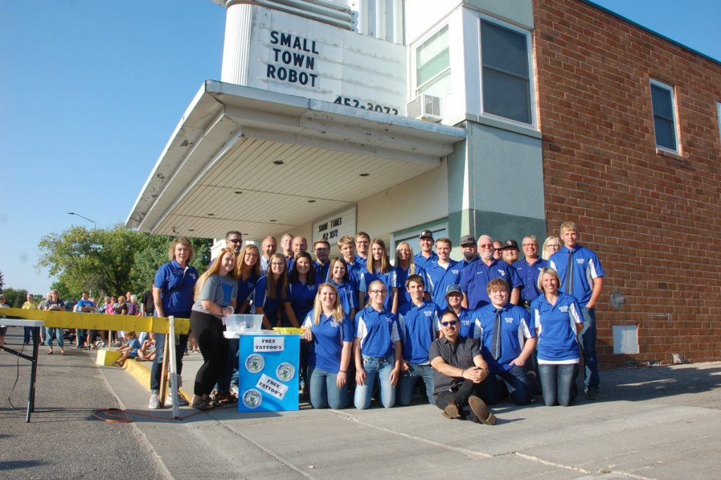 """Joe Brandmeier (sitting in front), the Greenbush-Middle River Robotics team, GMR Superintendent Tom Jerome (third from left in back row), and a FIRST Robotics representative (fourth from left in back row), pose for a photo together in front of the Roso Theatre in Roseau on August 15 prior to the premiere of """"Small Town Robot"""", a short documentary film by director and producer Brandmeier highlighting the GMR Robotics team and FIRST Robotics in general. An estimated 225 to 250 people filled the 300-seat theatre to watch this documentary. (photo by Ryan Bergeron)"""