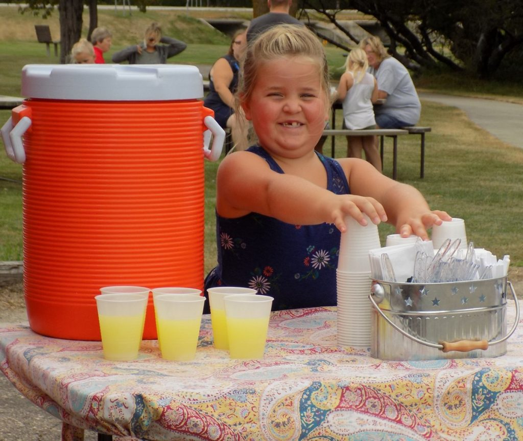 Not only was Amity Foss in charge of pouring lemonade, but she also made sure to hold down the empty plastic cups so they wouldn't be blown away by the gusty winds. (photo by Mavis Gonshorowski)