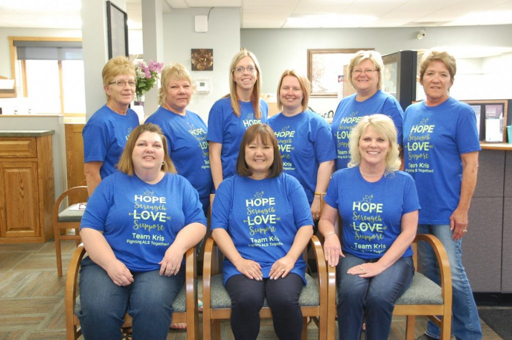 """The Border State Bank employees in Badger wore their """"Team Kris"""" t-shirts on Friday, July 19 to show support to former coworker Kris Jenson, who is battling ALS. They are (L-R): Front: Sharla Kilen, Natali Anderson, and Christine Modahl; Back: Joyce Shimpa, Lynn Norberg, Whitley Aamodt, Barb Monsrud, Sharon Heggedal, and Sandy Duray; Missing: Deb Pries and Tamara Nelson. Some Border State Bank employees attended the ALS Walk/Run in Roseau on July 20 in Kris' honor. (photo by Ryan Bergeron)"""