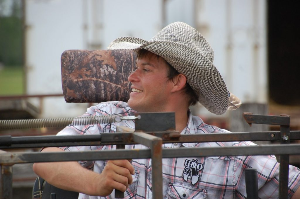 After opening up the chute doors to release a steer, Willy Westman smiles as he watches his cousin Kally Wojciechowski and uncle Keith Wojciechowski ride atop their stallions to chase down and rope this steer at the Wojo Arena located in rural Greenbush. While in the hospital for a couple months, Willy went through a rough time, but he told himself that he needed to get up and stop doing what he was doing. The rodeo life and the Wojciechowski farm provide him one outlet to get out of this rut. (photo by Ryan Bergeron)