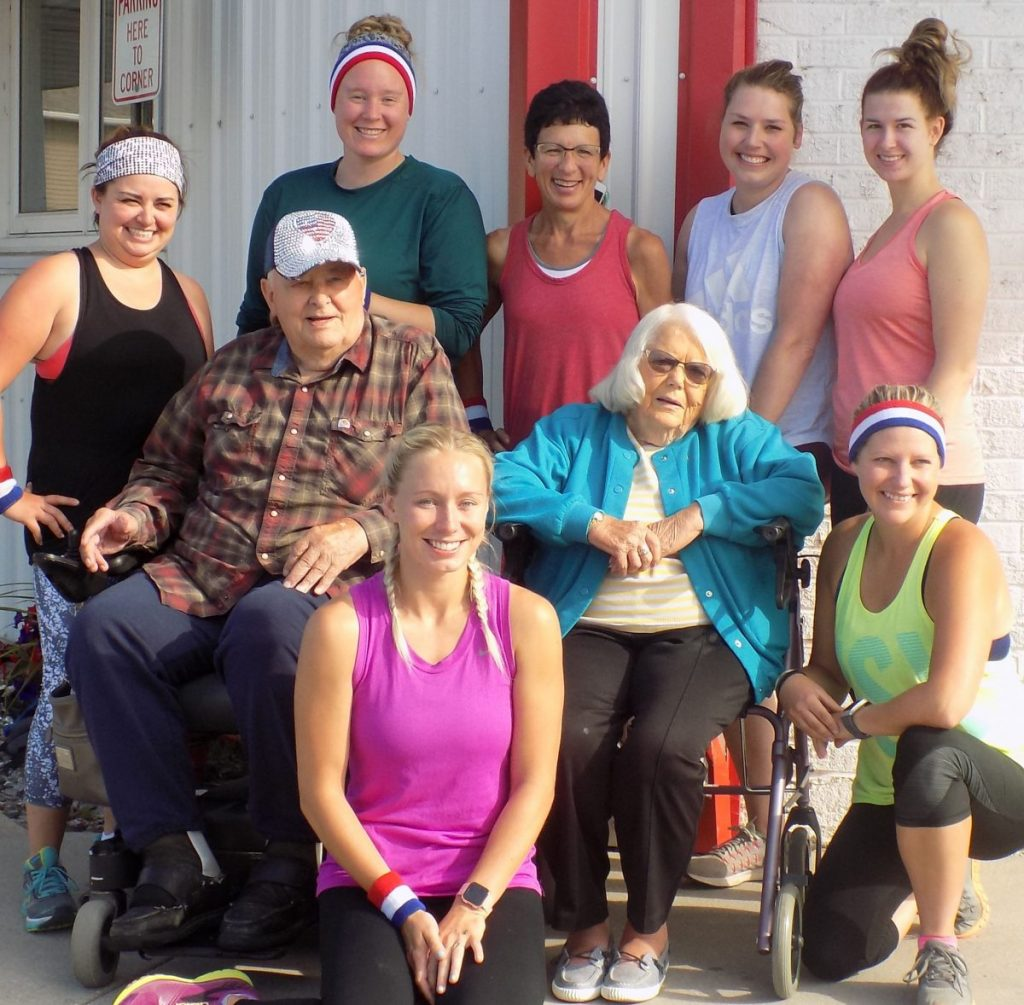 """""""Snooky"""" (Sheldon) and Helen Erickson, LifeCare Greenbush Manor residents, are pictured with the """"Greenbush Runners"""". Left to right, back row are: Amanda Kjos, Kayla Klaski, Karen Hedman, Paige Langaas, and Kasey Pries; front row: Chelsey Hamness and Kirsti Converse. (photo by Mavis Gonshorowski)"""