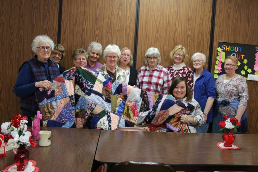 "Participants in the ""Crafts & Companionship"" Program at Newfolden, Minn. show the quilt they are raffling off. Tickets are $1.00 each and may be purchased at the Newfolden Center."
