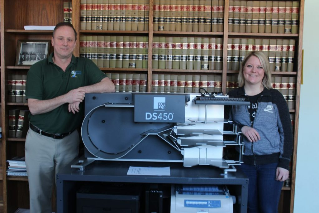 Photo: Kittson county  administrator, Eric Christensen, and staff member Britta Potrament pose with the central ballot tabulator that will count ballots for the March 3 election.