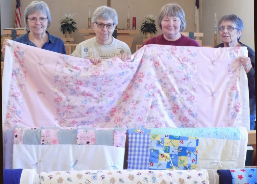 These quilts are but a few of the beautiful quilts made by the ladies of Gustav Adolph church in Strathcona. Shown left to right are: Connie Westlund, Karen Nelson Joan Dvergsten, and LaVon Coltom. (photo by Mavis Gonshorowski)