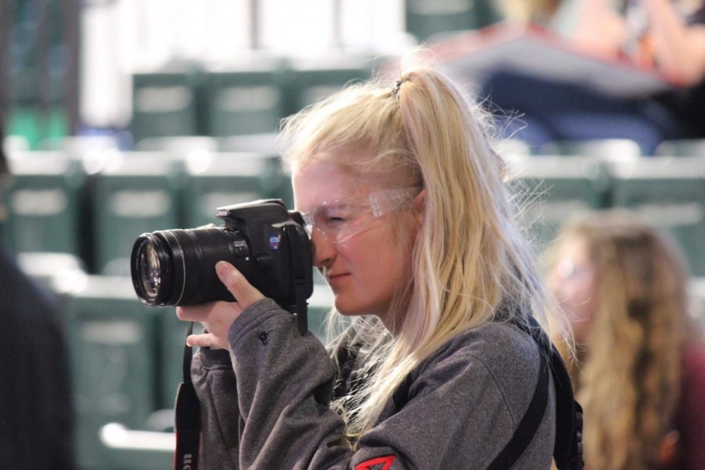 Greenbush native Emily Wicklund focuses in while taking a photo at a FIRST Robotics event. Wicklund takes photos at various events, such as robotics and snowmobile racing. (submitted photo)
