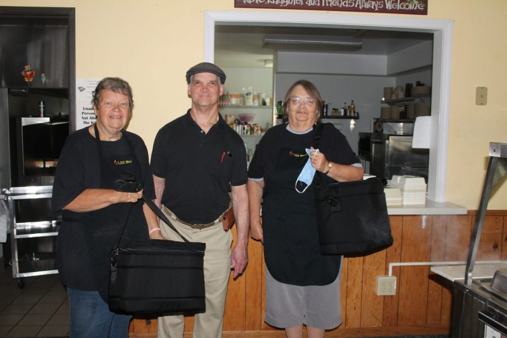 These Lutheran Social Services (LSS) employees at the LSS site in Karlstad find enjoyment in delivering meals. They, however, wouldn't mind some volunteer help - for just one day a week or Monday through Friday. Pictured are Mar-garet Donaldson (Karlstad site manager & cook), Richard Wood (cook's helper), Idell Klegstad (dining manager in Lake Bronson & kitchen assistant in Karlstad).