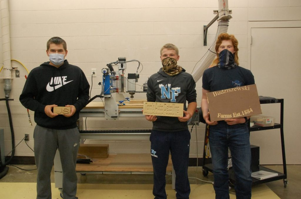 "Tri-County senior Construction class students (L-R) Jaacks Spilde, Jackson Spilde and Anton Budziszewski each hold one of the projects they completed with the class' new CNC router, the machine sitting behind them. As their teacher Brad Thompson said, this machine allows for ""limitless"" choices, such as drilling, carving and engraving. (photo by Ryan Bergeron)"