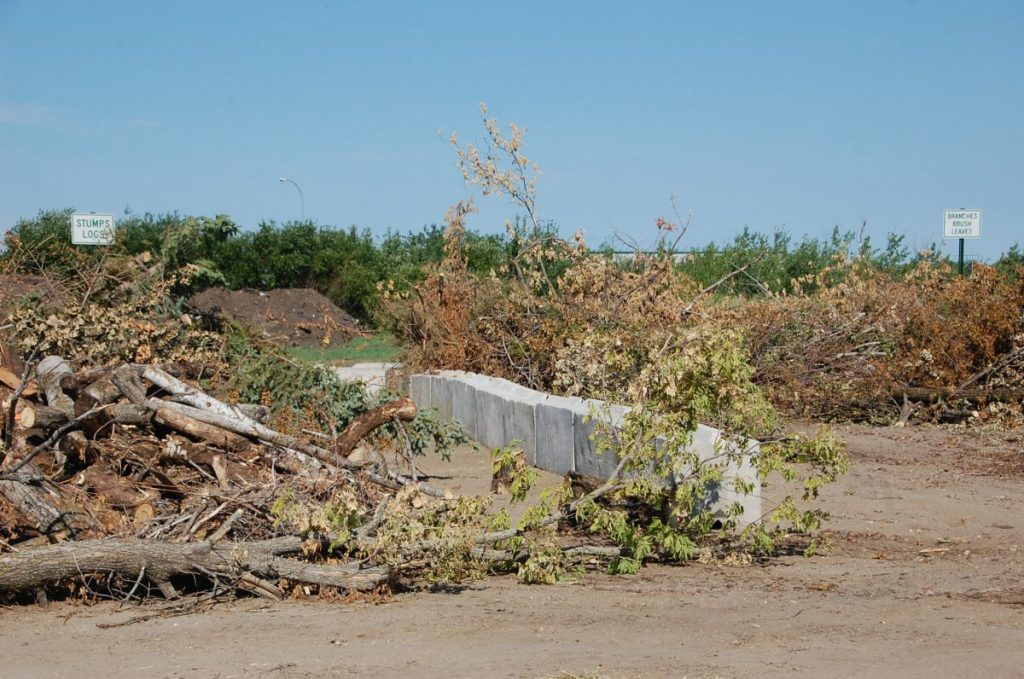 The three sections of the Karlstad Compost Site are distinguished from one another by not only blocks, but also the signage pictured here. One pile is for stumps and logs, a second one for branches, brush, and leaves, and a third one for grass clippings and garden waste. The site is open 24/7. (photo by Ryan Bergeron)