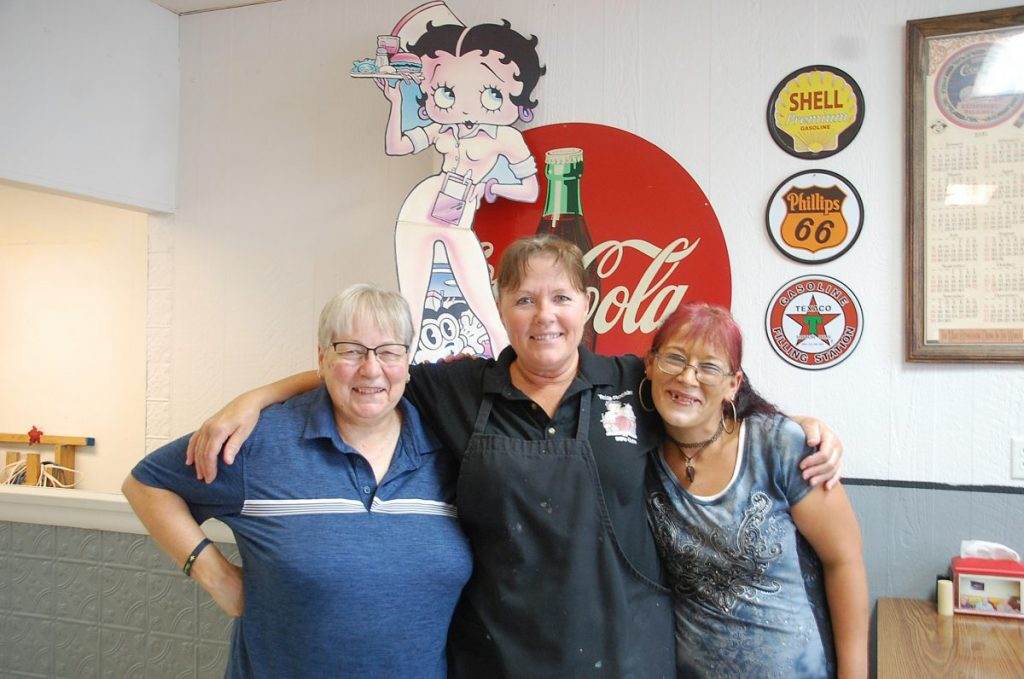 Sonia Lee (center), owner of Twins Rockin 50's Cafe in Greenbush, poses with her two waitresses, Nancy Goslein (left) and Abby Stauffer (right) after they put in their final shift at the cafe. After nearly 19 years in business, Lee closed the cafe's doors for business permanently following lunch on August 31. (photo by Ryan Bergeron)
