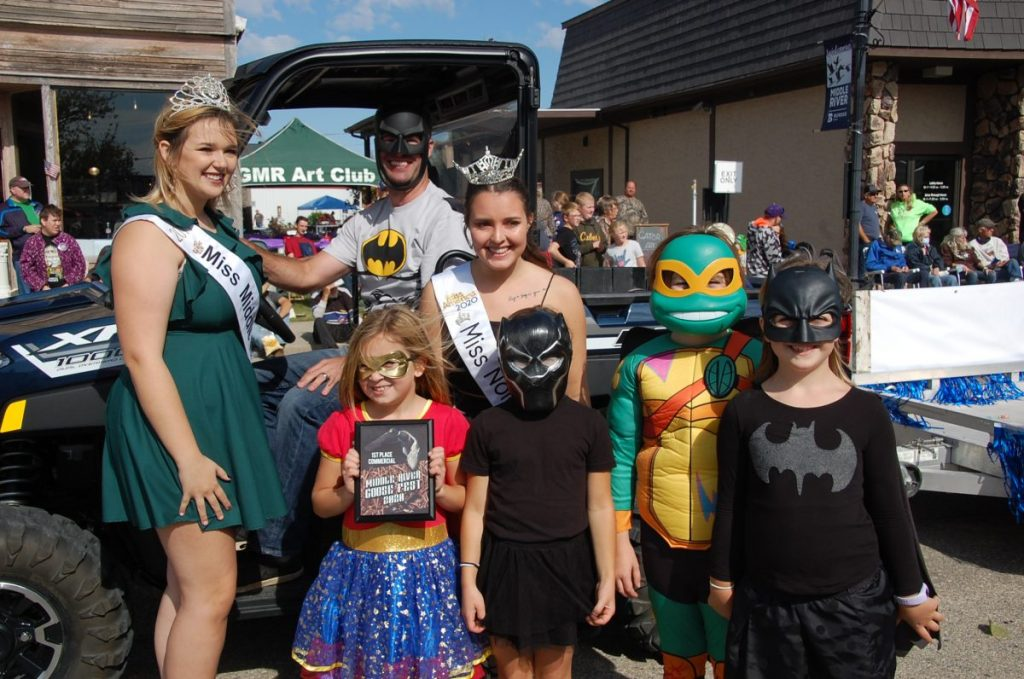 Now former Miss Middle River Piper Sondreal (left) and now former Miss North Star O'Brien Stromsodt (right) pose with representatives of the Border Bank float, each sporting super hero attire. The float earned first place in the commercial category at last year's Goose Fest Parade in Middle River back on September 26, 2020. (photo by Ryan Bergeron)