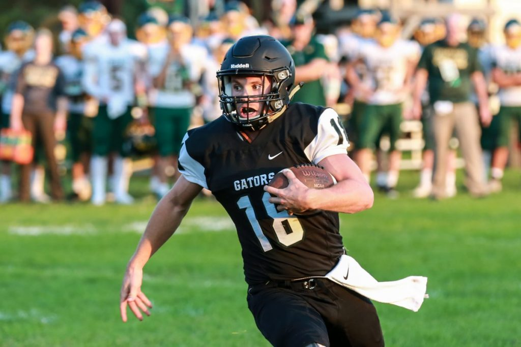 Gator quarterback Kobey Dallager runs with the ball during the Gator Football team's 43-23 home loss to the Nevis Tigers to open the 2021 season. Dallager threw for 185 yards and one touchdown pass and rushed for 70 yards and two touchdowns. (photo by Val Truscinski)